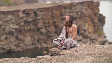 Yogi sitting on the rock near the sea ビデオ