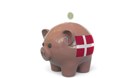 Putting money into piggy bank with flag of Denmark. Tax system system or savings Live Action