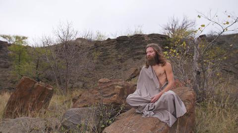 Yogi sitting on the rock in meditation ビデオ