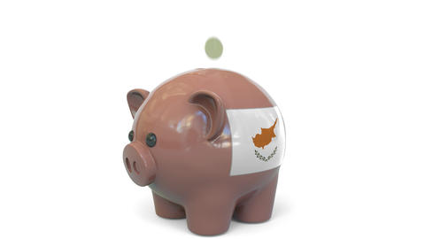 Putting money into piggy bank with flag of Cyprus. Tax system system or savings Live Action