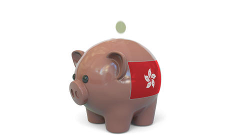 Putting money into piggy bank with flag of Hong Kong. Tax system system or Live Action