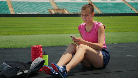 Young girl athlete uses a mobile phone in a stadium ビデオ