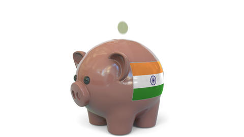 Putting money into piggy bank with flag of India. Tax system system or savings Live Action