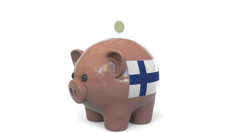 Putting money into piggy bank with flag of Finland. Tax system system or savings Live Action