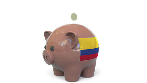 Putting money into piggy bank with flag of Colombia. Tax system system or Live Action