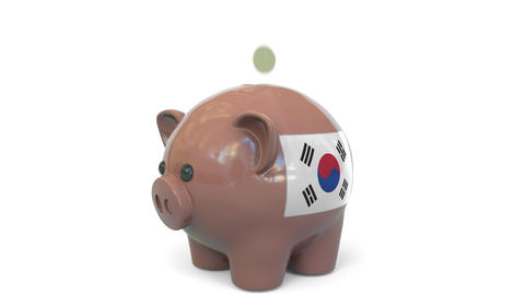 Putting money into piggy bank with flag of South Korea. Tax system system or Live Action