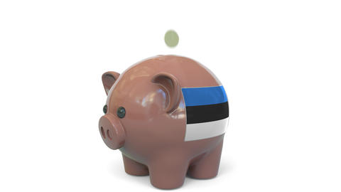 Putting money into piggy bank with flag of Estonia. Tax system system or savings Live Action