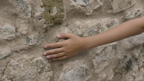 Young hand touching old stony wall outdoor. Close up teenager hand touching Live Action