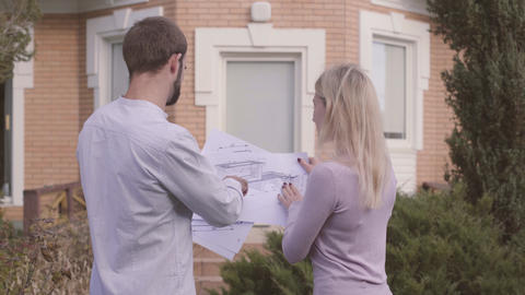 Young female Caucasian constructor showing the project to customer. Handsome man Footage