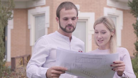 Close-up of two Caucasian architects discussing blueprints outdoors Footage