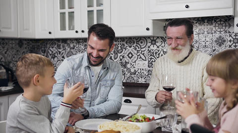 Laughing cheerful father and grandpa with cute boy and girl sitting at the table Footage