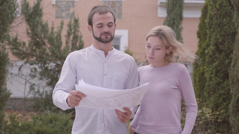 Two Caucasian designers examining architectural drawings outdoors. Annoyed woman Live Action