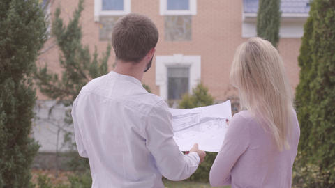 Two young Caucasian people standing with architectural drawings and talking Live Action