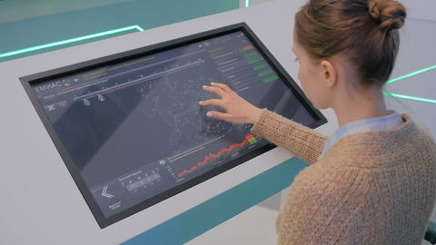 Woman using interactive touchscreen display at modern museum or exhibition Live Action