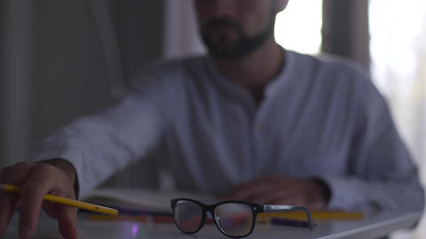 Blurred Caucasian man working with papers at the background. Male professional Footage