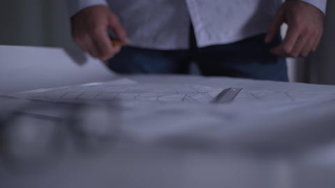Close-up of architectural drawings lying on the table. Irritated man putting Live Action