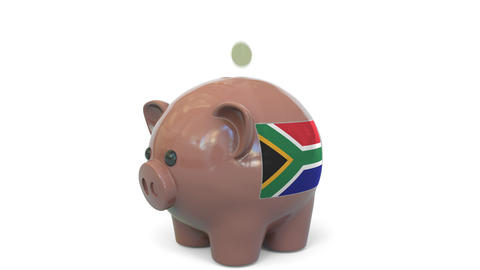 Putting money into piggy bank with flag of South Africa. Tax system system or Live Action