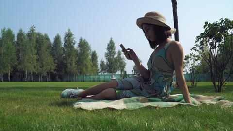 Young brunette girl sitting on blankets in the park and gaining a message on the Footage