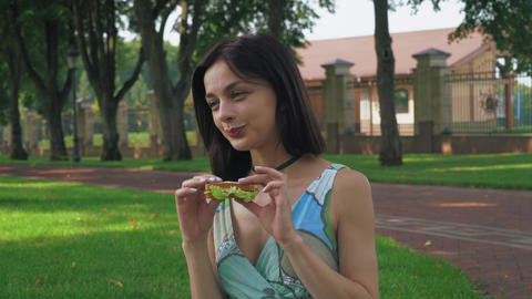 Attractive brunette girl eating a sandwich in the park Footage