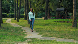 Young brunette girl is on a path in the park Footage