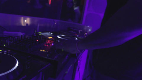 Afro DJ set in nightclub, wide and close-up, turntable buttons, dancing people Footage
