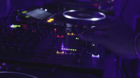 Afro dj playing tweaking equipment (mixer, turntable, tractor) in nightclub Footage