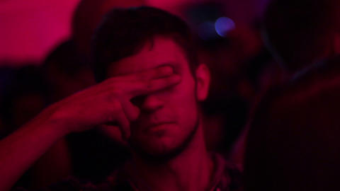 Funny man hides his face with fingers in nightclub Footage