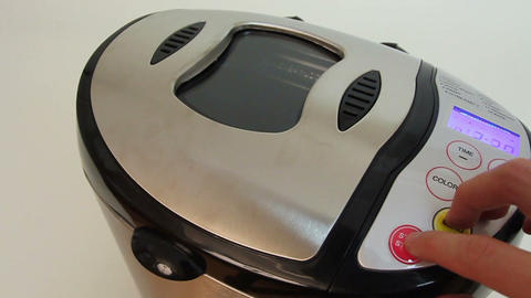 Hand presses buttons on bread machine's panel for baking Footage