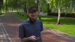 A young boy goes on a path in a park near the building and gaining a message on  Footage