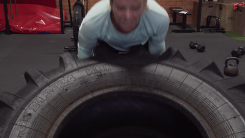 Woman doing tire flips power lifting workout at gym Live Action