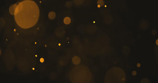 abstract gold glow particles bokeh flowing effect on black background, holiday happy new year Live Action