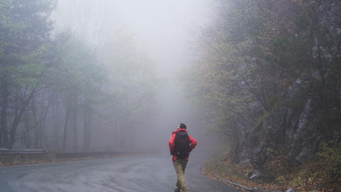 Person with red raincoat and black backpack Stands On Foggy Asphalt Road Live Action