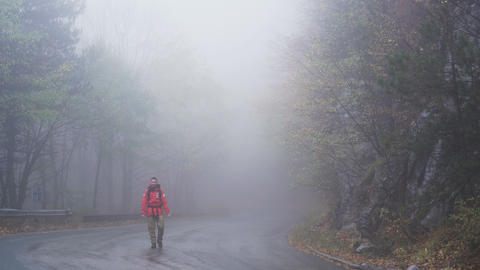 Carefree man dancing in the rain, walking happily on foggy road Footage