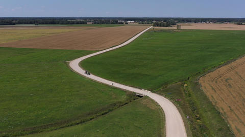 beautiful summer gravel road bends in farmland and agriculture tractor, aerial view Live Action