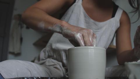 Female potter molding wet clay pot with wet sponge Live Action