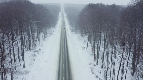 Aerial view of traffic on a road surrounded by winter forest in snowfall Archivo