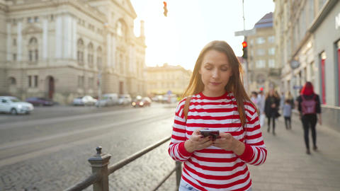 Young woman walking down an old street using smartphone at sunset. Communication Archivo