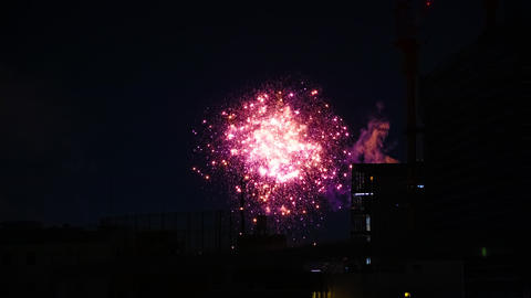 A timelapse of fireworks near the building at the urban city in Tokyo at summer Live Action