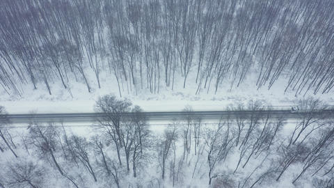Aerial view of traffic on the road passing through the winter forest Archivo