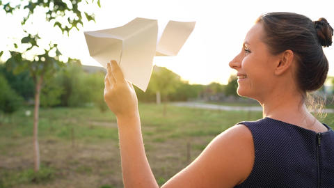 Woman launches paper airplane against sunset background. Dreaming of traveling Footage