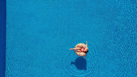Aerial view of a woman in red bikini lying on a donut in the pool Archivo