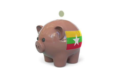 Putting money into piggy bank with flag of Myanmar. Tax system system or savings Live Action