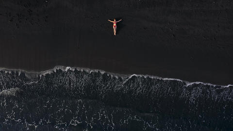 Top view of a woman in a red swimsuit lying on a black beach on the surf line ビデオ
