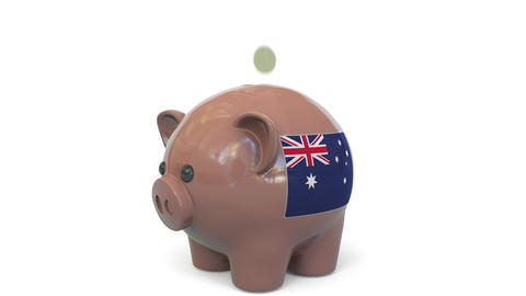 Putting money into piggy bank with flag of Australia. Tax system system or Live Action