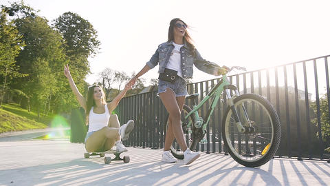 Caucasian young woman sitting on a longboard while her best female friend goes Footage