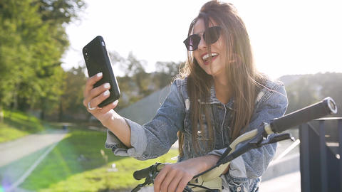 Portrait of pretty cheerful caucasian girl in sunglasses with bicycle, making Footage