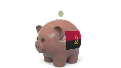 Putting money into piggy bank with flag of Angola. Tax system system or savings Live Action