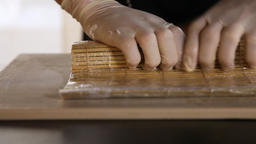 Close-up of chef's hands rolling a sushi roll on bamboo mat.Sushi making process Live Action