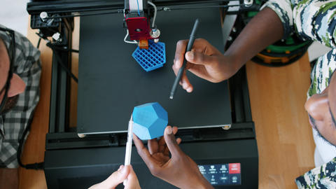 Male designers holding 3d printed shape discussing design while machine printing Live Action