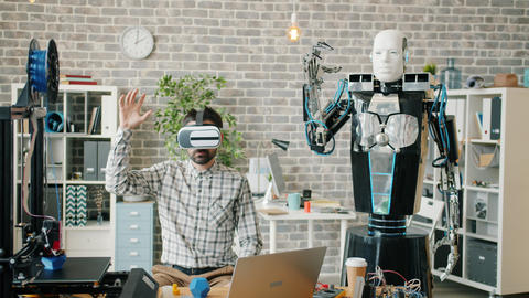 Man wearing ar glasses moving hand robot repeating movements in office Footage